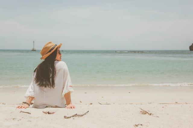 Žena v bielej blúzke a klobúku sedí na pláži pri mori.jpg