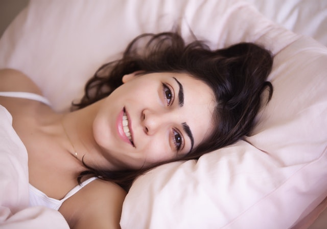 Hnedovlasá usmiata žena leží na bielom vankúši