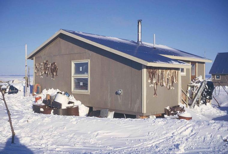 Mobilné domy sivej farby postavené vedľa seba v zasneženej krajine