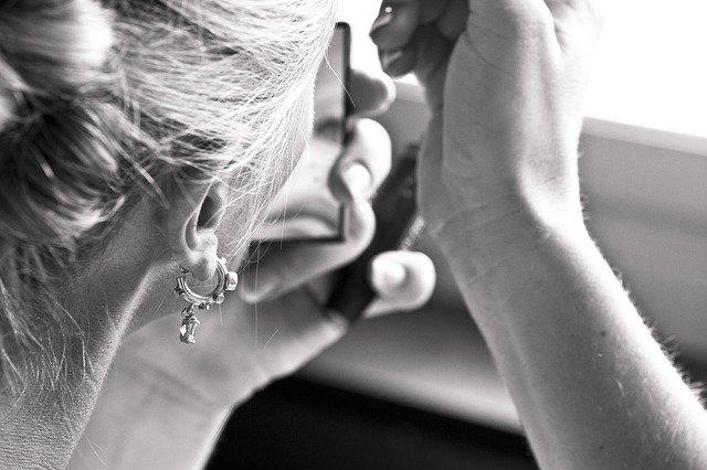 Detail na ucho ženy s náušnicou, ktorá sa maľuje pri malom zrkadielku.jpg